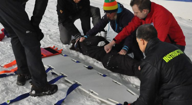 Image of casualty being put on board in snow environment
